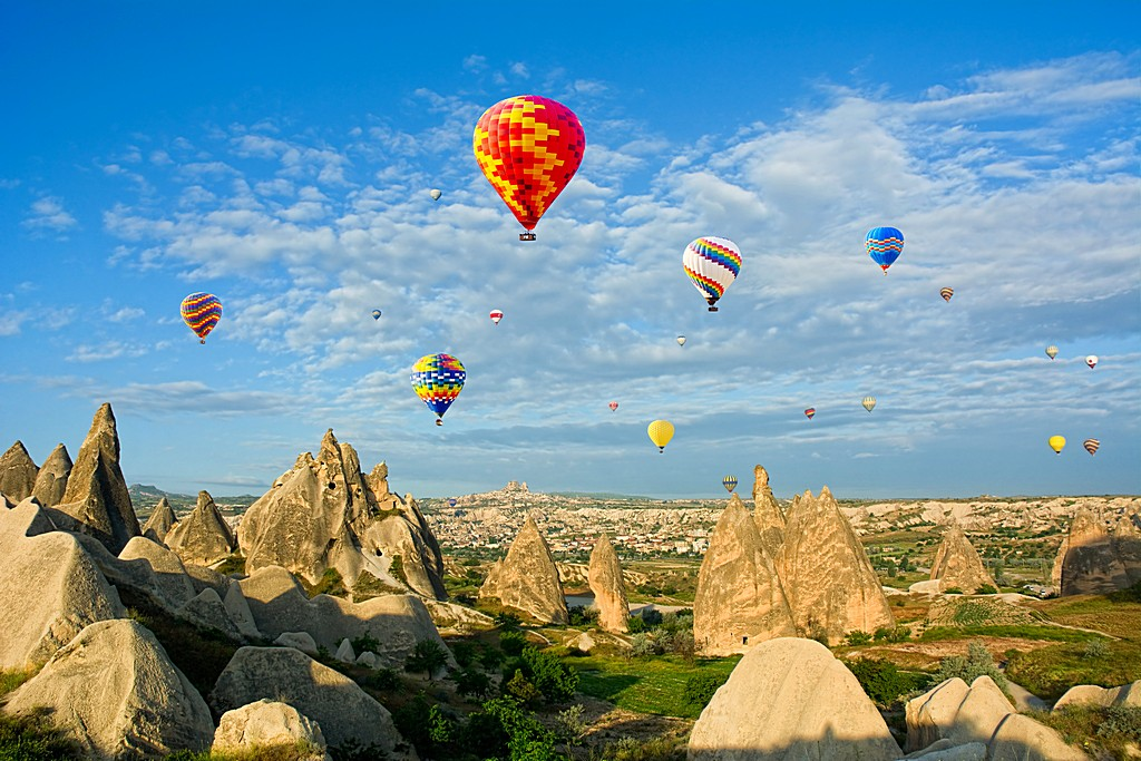 Colorful hot air balloons flying over volcanic cliffs at Cappado