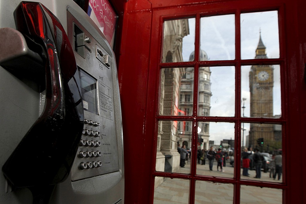 Government buildings and the Big Ben Clock Tower are pictured through a traditional red phone box in London